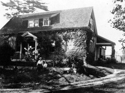 two people in front of large brick house covered in ivy