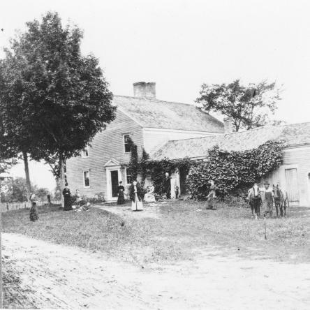 corner-wise view of house with vegetation and people in front